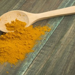 turmeric powder and wooden spoon