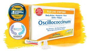 Oscillococcinum box and tube with pellets spilled out, against yellow and orange watercolor background and PTPA and Pharmacy Times awards