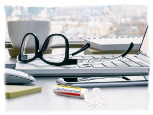 Tube of Oscillo with pellets spilled out on work desk next to phone, sticky pad, mouse, laptop, eyeglasses, books, and coffee mug, in front of window with city in background