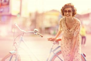 girl laughing next to bicycle